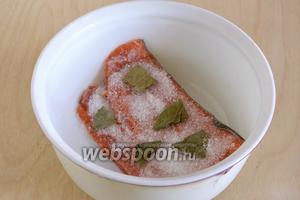 Поместите рыбу кожей вниз в стеклянную или керамическую посуду. Посыпьте солью, сахаром и разломанным на кусочки лавровым листом.