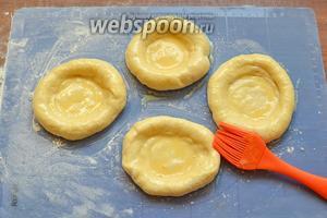 Смазываем лепёшки желтком, в смеси с молоком, и укладываем их на формочку, смазанную маслом.