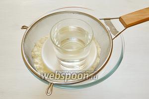 Для крема и украшения мне нужен сухой зернистый творог. Выкладываем его в сито, чтобы отделить сливки от творога, накрываем блюдцем и ставим небольшой груз.