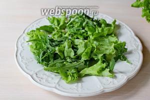 На блюдо выложить промытые и обсушенные листья салата и рукколу.