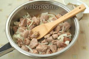 В сковороде разогреть масло и обжарить кусочки индейки до лёгкого золотистого цвета. Добавить лук и жарить до мягкости.