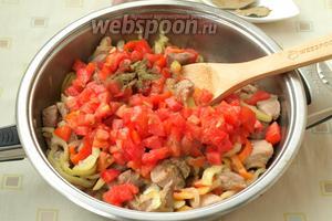 Кубиками нарезать помидоры, добавить их следом за перцем. Также добавить приправу хмели-сунели, соль и перец. Тушить всё вместе около 8 минут, периодически помешивая.
