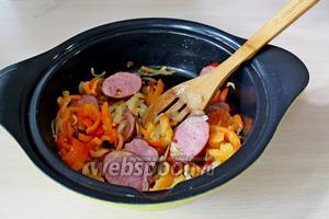 На оливковом масле обжариваем (в течение 2 минут) лук с чесноком, затем 2-3 перчины (сладкого и острого). И 2 минуты жарим колбасу вместе с овощами.