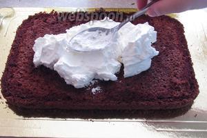 Выложить часть сливок на пропитанный корж и выровнять слой.