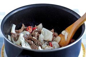 К обжаренному и тушёному мясу добавить лук, острый перец и чеснок. Обжарить до прозрачности лука.