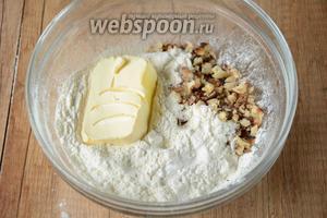 В просеянную муку добавить орехи и размягчённое сливочное масло.