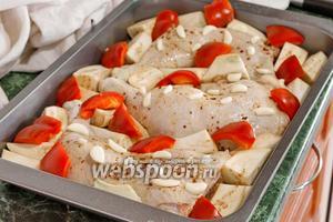 Добавляем баклажаны, перец и пластинки чеснока в деко к окорочкам.