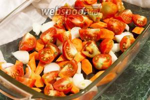 В деко выкладываем морковь, лук и помидоры, нарезанные четвертинками.