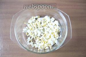 Яйца отварить вкрутую, охладить, почистить и нарезать кубиками. Выложить в салатник.