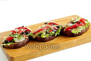 На кусочки хлеба выложить зелёный салат, а поверх разложить содержимое тарелки. Брускеты готовы. Приятного аппетита!