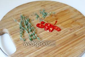 Чили перец нарезать на тонкие колечки, у веточек тимьяна отделить листики и добавить их в суп.