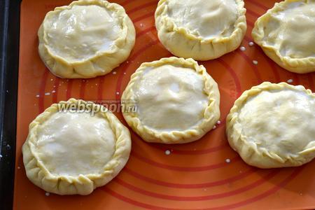 Выложить заготовки элешей на противень с пекарской бумагой. Смазать сливками или растопленным сливочным маслом.