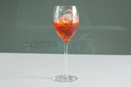 После заполнения льдом, бокал приблизительно на 1/3 заливается аперитивом.