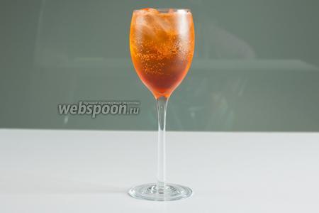 Поверх аперитива доливается или вино и газировка, или игристое вино. Если льда не пара кубиков, а много, или вы промедлите лишнюю минутку с игристым, может случиться так, что аперитив «замёрзнет», ляжет на дне и не пожелает смешиваться с игристым. В этом случае покрутите в бокале барной ложечкой: «шприц» — не слоистый коктейль, на момент подачи он должен быть окрашен равномерно.