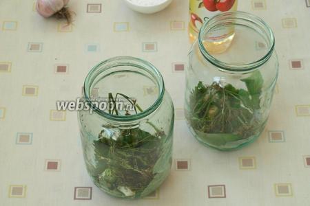 В чистые банки, объёмом 1 л, на дно выложить зонтики укропа, листья малины, зубки чеснока, кусочек острого перца.