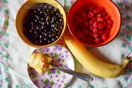 Возьмём свежие или замороженные ягоды: малину и чёрную смородину, банан и мёд.