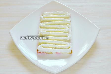 На 1 полоску бисквита, пропитанную сиропом, выкладываем крем.