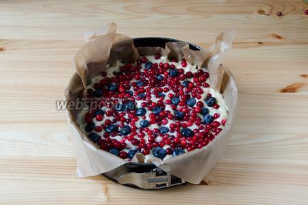 Форму, в которой будет выпекаться пирог, застилаем пергаментной бумагой. На дно формы выкладываем 1/2 теста. Сверху выкладываем половину ягод, слегка утапливая их в тесто. Выливаем вторую половину теста и выкладываем оставшиеся ягоды. Ягоды тоже необходимо слегка утопить в тесте.