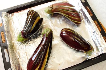 Баклажаны выкладываем на противень, застеленный фольгой, сбрызгиваем маслом.