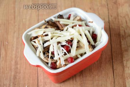 Сыр натереть на крупной тёрке, сверху на грибы и клюкву. Поставить форму в разогретую до 180°С духовку на 25 минут. Готовое блюдо подавать в горячем виде. Приятного аппетита!