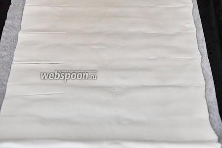 На пергаменте раскатать тесто в прямоугольник. Сделать параллельные горизонтальные надрезы на расстоянии примерно 4 см с обеих сторон.