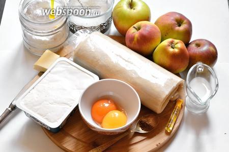 Для приготовления яблочного кольца со сливочным сыром подготовим продукты: яблоки, слоёное тесто (предварительно полностью разморозить), куриные желтки, сливочный сыр, сахар, сахарную пудру, экстракт ванили, корицу, молоко и сливочное масло.