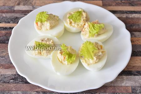 Затем начиняем яйца и украшаем листьями салата или же пекинской капустой.