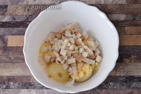Итак, кальмаров и яйца предварительно отвариваем. Затем, в глубокую тарелку, отделяем желток и нарезаем кальмаров кубиками.