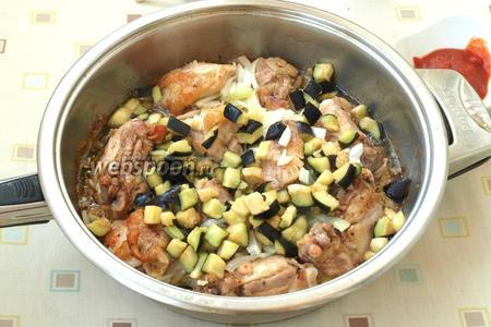 Затем курицу перевернуть, добавить в сковороду нарезанный четверть кольцами репчатый лук, следом добавить баклажаны, отжав их от жидкости. Жарить курицу с луком и баклажанами 10 минут на среднем огне, при необходимости помешивая.