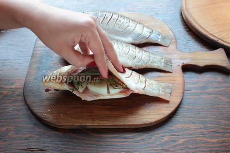 В брюшко закладываем нарезанный колечками лук, тимьян.