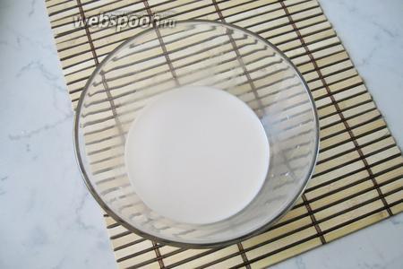 Молоко и воду налить в миску, подогреть до тёплого состояния. Выложить дрожжи и 1 столовую ложку сахара, перемешать.