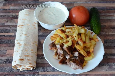 Для приготовления турецкой шаурмы вам понадобится лаваш, огурец, помидор, чесночный соус для шаурмы, мясо обжаренное, картофель жареный.