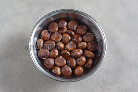 Каштаны придётся чистить сырыми, да так, чтобы удалось дочиста снять с них мохнатую шкурку, находящуюся между орехом и блестящей внешней кожурой. Для этого неочищенные каштаны помещаются на 1 сутки или чуть больше времени в воду.
