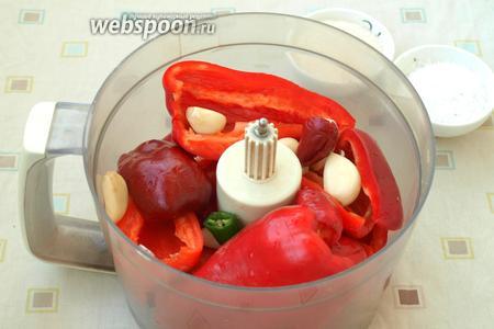 В чашу комбайна частями сложить перцы и чеснок.