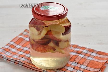Выложить яблоки в стерилизованную банку и залить крутым кипятком с лимонной кислотой. Закрыть крышкой и оставить на 5 минут.