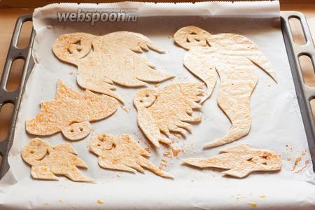Выкладываем привидений на противень, на кондитерскую бумагу, обмазываем сверху маслом с солью и с приправами.