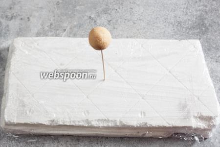 Втыкаем палочки в кейк-попсы и устанавливаем их вертикально (удобнее всего — в панель из пенопласта, покрытую фольгой или пищевой плёнкой из гигиенических соображений).