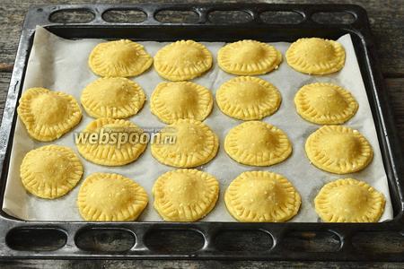 Выложить пирожки в форму для выпечки, выложенную кулинарной бумагой.