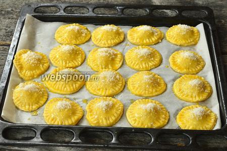 Смазать пирожки разболтанным желтком с небольшим количеством белка и посыпать сахаром.