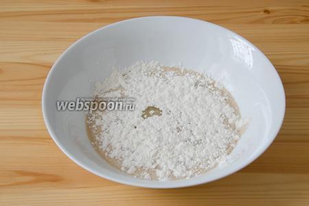 В слегка тёплое молоко высыпаем сухие дрожжи. Туда же добавляем сахар, 2 столовых ложки растительного масла и 2 столовых ложки муки. Накрываем полотенцем и отставляем в сторону на 15 минут.