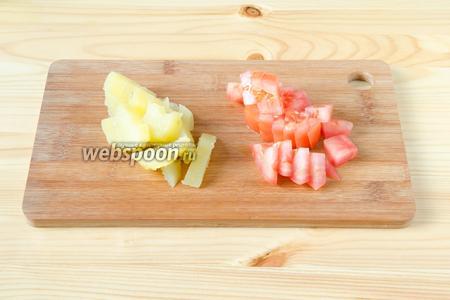 Отварной картофель и помидор режем небольшими кубиками.