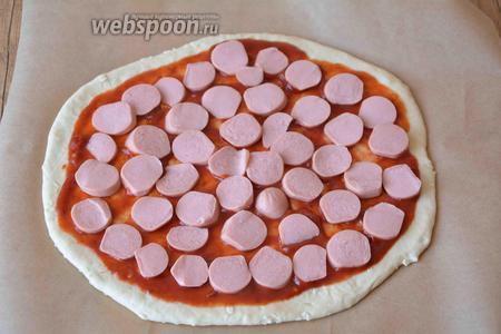 Средними кусочками нарезаем сосиски, раскладываем их по всей поверхности пиццы.