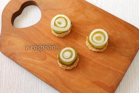 Выкладываем на хлеб кружочек огурца и 2 кольца лука, подходящие по диаметру.