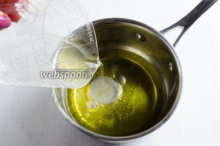 Масло влить в сотейник. Добавить горячую воду (кипяток). Перемешать.