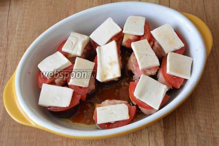 Плавленый сыр порезать тонкими пластинами. Выложить сыр сверху на помидор. Оставшуюся заправку выливаем в форму для запекания. Убираем форму в разогретую, до 200°С, духовку на 25 минут.