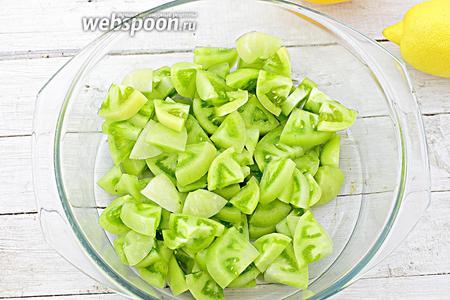 Итак, начните с подготовки помидор. Отберите плотные плоды зелёного цвета, без механических повреждений и чёрных пятнышек. Предварительно, перед готовкой, тщательно промойте и замочите на пару часов в растворе холодной воды и соды (на 1 л воды возьмите 1 ч. л. соды). После, хорошо промойте и обсушите салфеткой. Разрежьте пополам, обрежьте место у плодоножки. Нарежьте небольшими дольками. Уложите в подходящую по размеру кастрюлю.