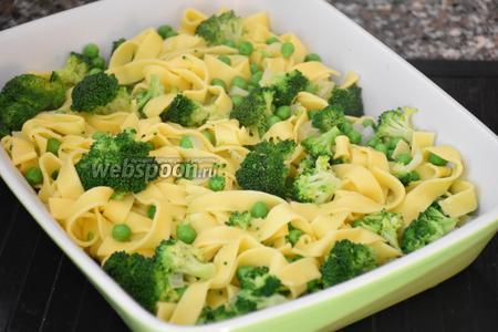 Форму для запекания смазать маслом и выложить лапшу с овощами.
