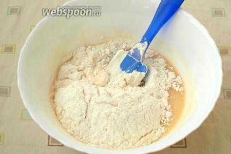 Постепенно просеять в тесто муку, сначала замешивая лопаткой, затем руками.