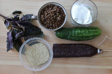 Для приготовления нужна отварная зелёная чечевица, колбаса суджук, огурец, кунжут. Для заправки — сметана и базилик.
