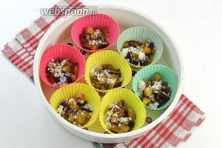 На дно силиконовых формочек для кексов выложить нарезанные на мелкие кусочки сливы и посыпать немного сахаром.